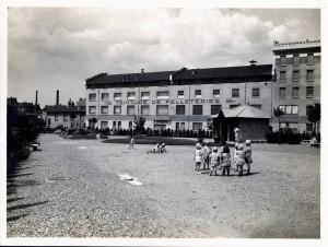 groupe d'enfants jouant avec en arrière plan, l'usine de teinture de peaux Lacourbat-Claret-Confavreux.(AMV 4Fi460)
